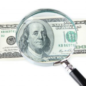magnifying glass over $100 bill